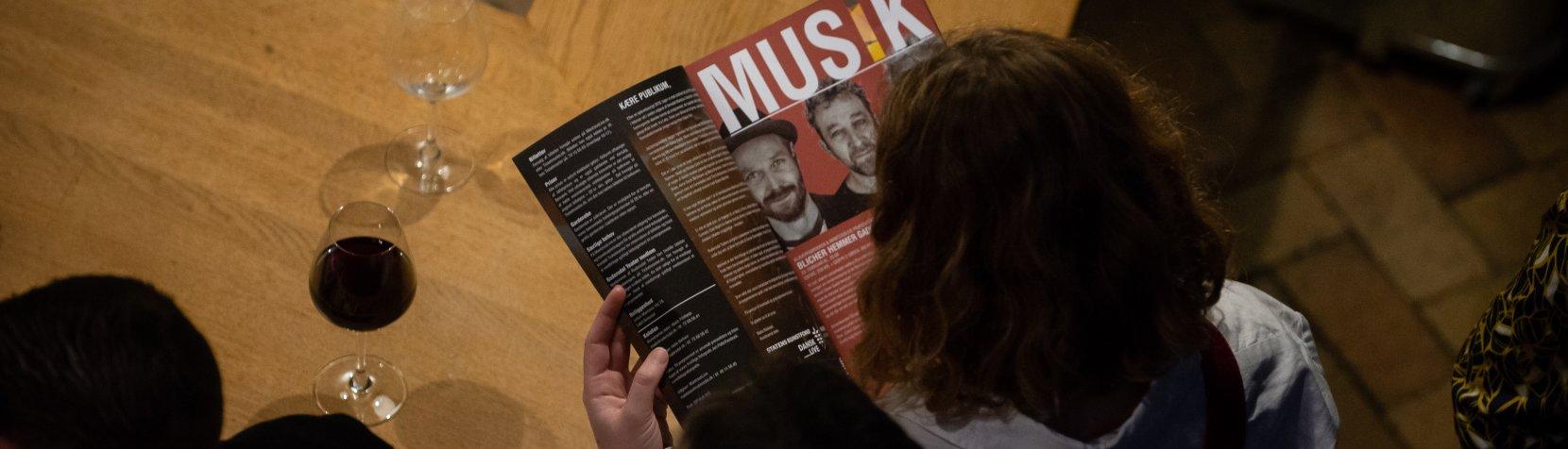 En gæst læser en side med overskriften MUSIK fra MantziusLives trykte program